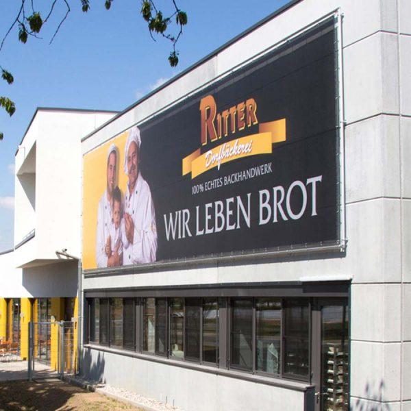 Gebäude und Objektgestaltung Banner im XXL Druck Fassadenwerbung am Beispiel der Dorfbäckerei Ritter in Vörstetten bei Freiburg