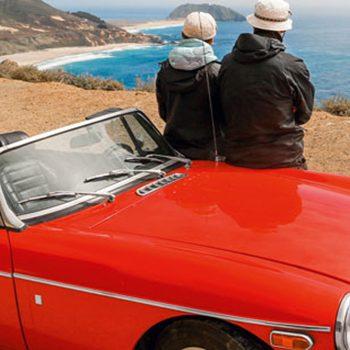Roter Oldtimer mit älterem Paar auf Amerikas Traumstraße